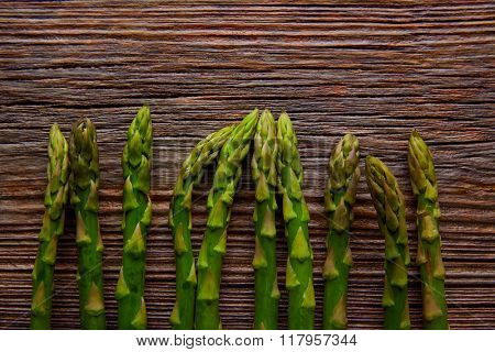 Asparagus raw vegetables in a row on aged wood background