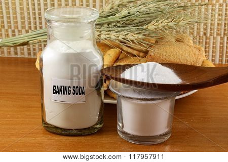 baking soda in a glass jar and wooden spoon with cookie and wheat
