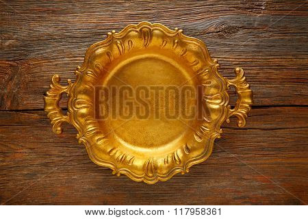Vintage golden tray round on an aged brown wood background