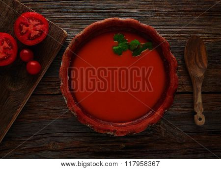 Tomato sauce on clay dish and dark wood background