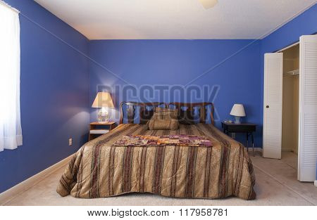 Dated simple bedroom with carpet and popcorn ceiling