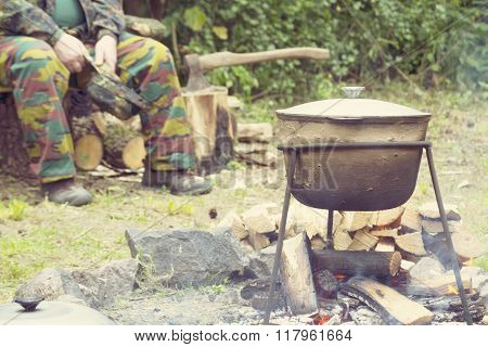 man in camouflage and  kettle for a hike