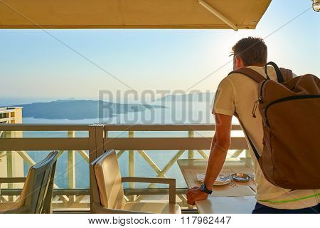 SANTORINI, GREECE - AUGUST 07, 2015: man posing in the cafe on Santorini island. Santorini, classically Thera, and officially Thira, is an island in the southern Aegean Sea