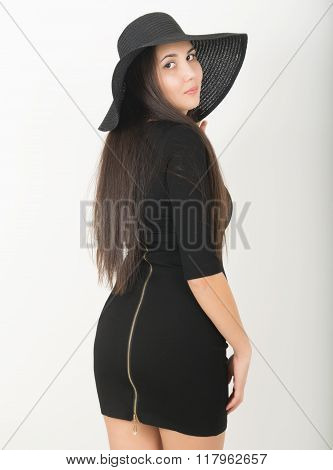 slender beautiful Asian girl in little black dress and a black wide-brimmed hat