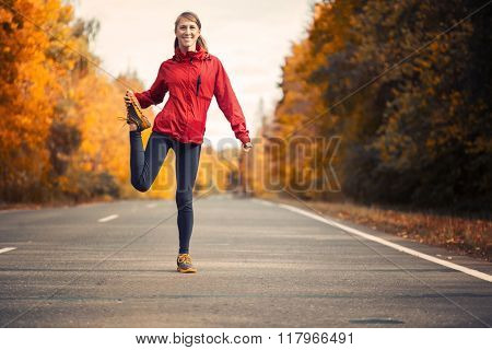 Woman warms up and stretches on an asphalt road in an autumn forest