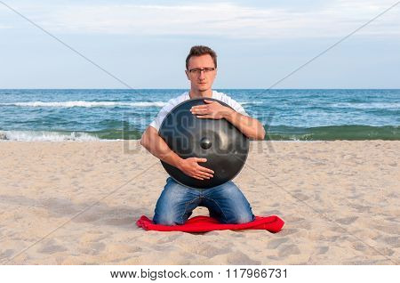 Young stylish guy sitting on the sand beach and holding a handpan or hang with sea On Background. Th
