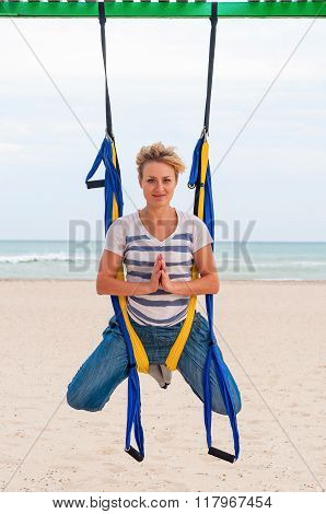 Fly-yoga, Anti gravity or fly yoga on the beach. Young woman doing yogas exercise. Yoga with hammock