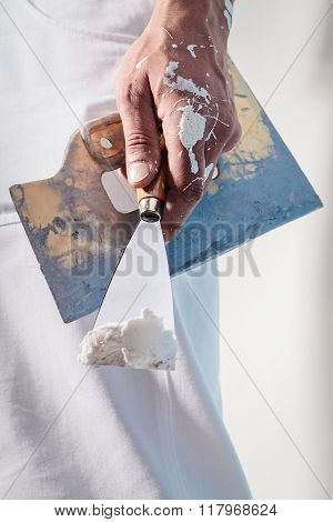 Workman Hand Holding Putty Knife With Plaster