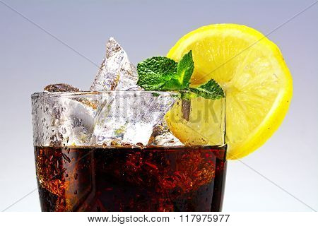 Top Of A Glass Of Cola Or Ice Tea With Ice Cubes, Lemon Slice And Peppermint Garnish