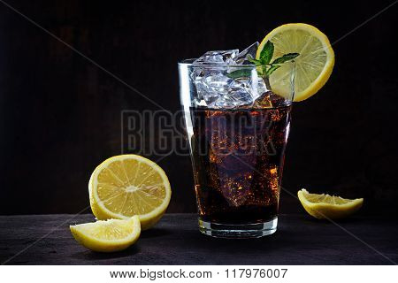 Glass Of Cola Or Ice Tea With Lemon Slices And Peppermint Garnish On A Wooden Table Against A Dark B