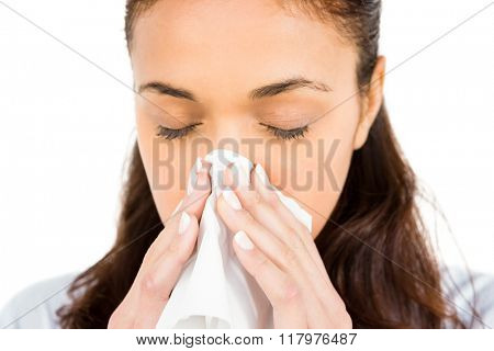 Woman blowing nose with tissue paper against white background