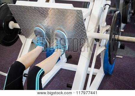 Fit woman doing exercises for legs at the gym