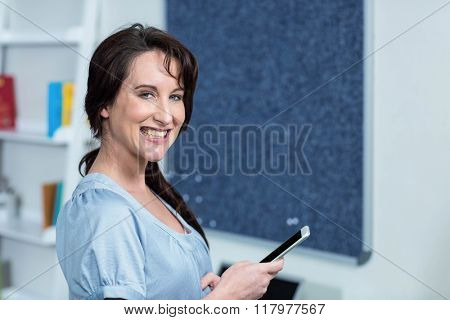 Pregnant woman with smartphone at home