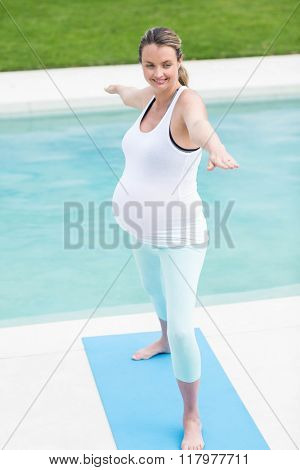 Pregnant woman doing yoga next to the swimming pool