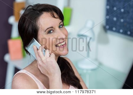 Pregnant woman on the phone at desk