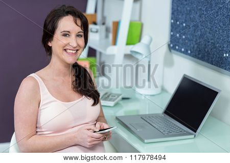 Pregnant woman on her smartphone at desk