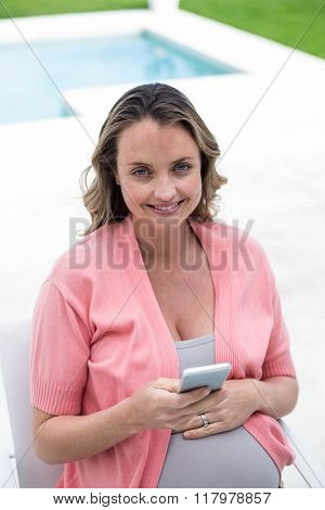 Pregnant woman texting by the pool