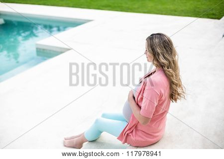 Pregnant woman touching her belly sitting next to the pool
