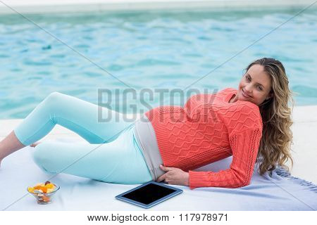 Pregnant woman relaxing outside and using tablet next to the pool