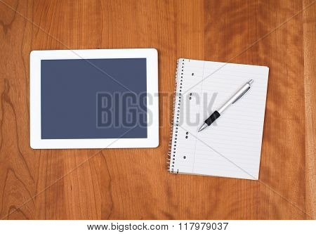 Tablet Pc And Notepad On Wooden Table From Above