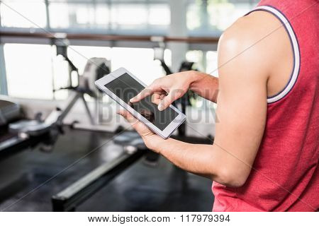 Mid section of man using tablet in the gym