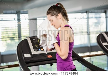 Tired brunette on treadmill wiping sweat with towel in the gym