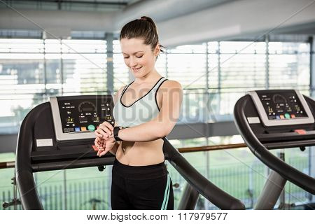 Smiling woman on treadmill using smart watch at the gym