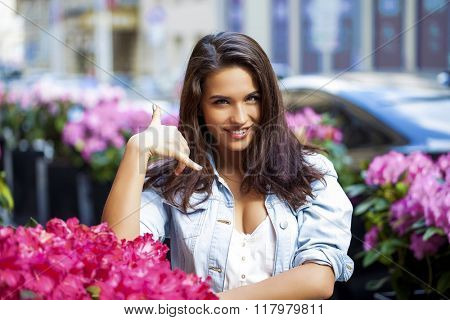 Portrait of attractive young woman on open air. Woman making a call me sign outdoors