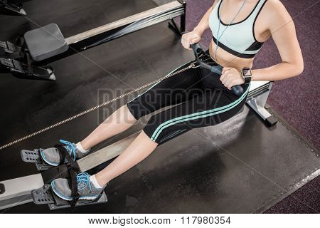 Low section of brunette on drawing machine at the gym