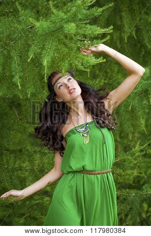 Beautiful young woman in green dress, against green of summer park