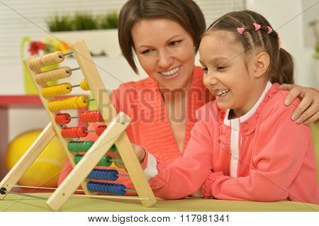 girl doing math exercises with  mother