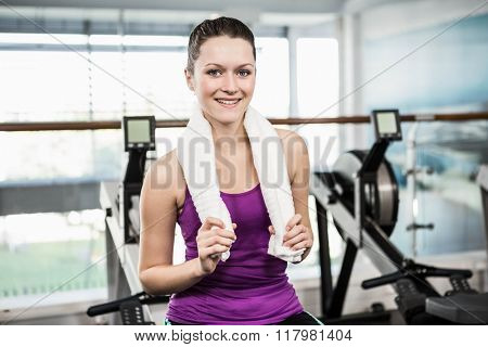 Smiling woman with towel around her neck at the gym