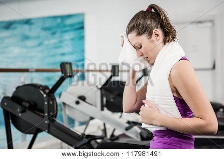 Fit brunette wiping sweat with towel at the gym