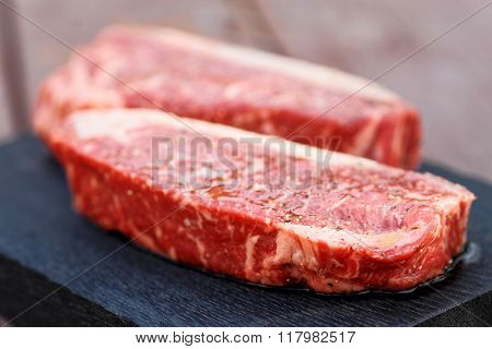 Two pieces of raw striploin steak on wooden plank, toned