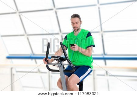 Young Man Train With Fitness Machine And Listening Music