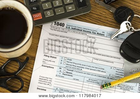 US tax form 1040 with pencil and calculator, coffee and keys.