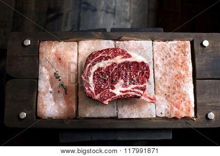 Bone In Rib Eye row Steak on pieces of salt