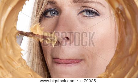 Woman Looking Ina Jar Of Peanut Butter With Chocolate