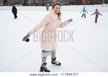 One young woman in pink jacket and ice-skates is standing on the rink.