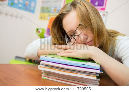 Tired young girl is sleeping with glasses on the textbooks.