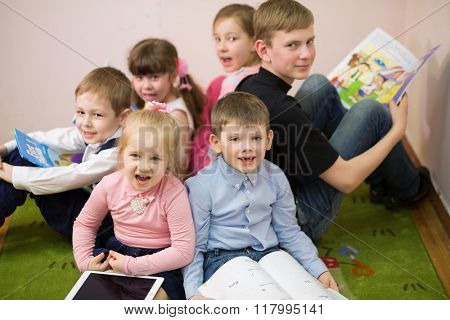 Six children are sitting on the floor with opened mouth.