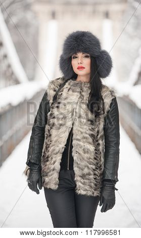 Attractive woman with black fur cap and gray waistcoat enjoying the winter