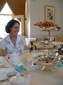 picture of bridal shower  - young woman smiling at proper tea service with three tier silver serving tray - JPG