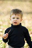 A Little Boy Eating Short Stick poster