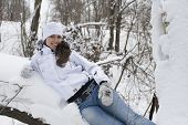 The young woman in a white jacket lies on a snow-covered tree
