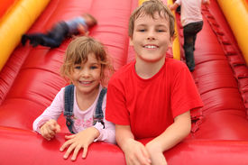image of inflatable slide  - little boy and girl lying on red inflatable slide smiling and looking at camera - JPG