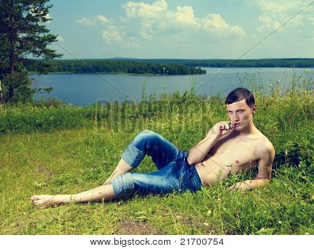 Young Man Lying On Meadow