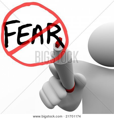 A person draws the word Fear and a red circle and slash over it with a red felt marker on a glass board, illustrating the determination to conquer fears and anxieties
