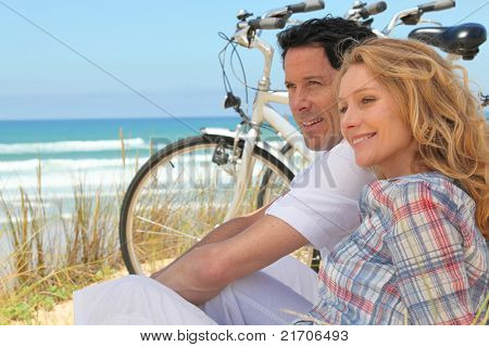 Profile picture of couple sat next to bicycles at the beach