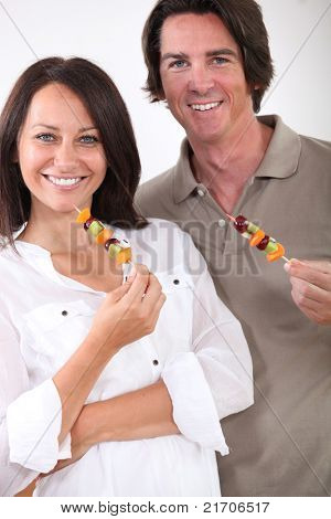portrait of a couple with fruit brochettes